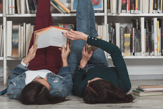 Two girls laying on the library floor reading.